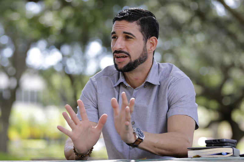 In this photo taken Wednesday, Nov. 8 2017, Javier Gonzalez talks to a reporter in Hialeah, Fla. Gonzalez has joined the tens of thousands of Puerto Ricans moving to Florida after Hurricane Maria, grateful for a place to start over but not without resentment over how his island was treated in the disaster. (AP Photo/Alan Diaz)