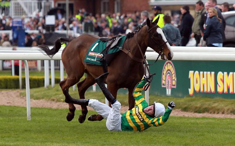 Synchronised, the favourite for the 2012 race, seen here unseating jockey Sir AP McCoy before continuing and falling - Credit: David Davies/PA