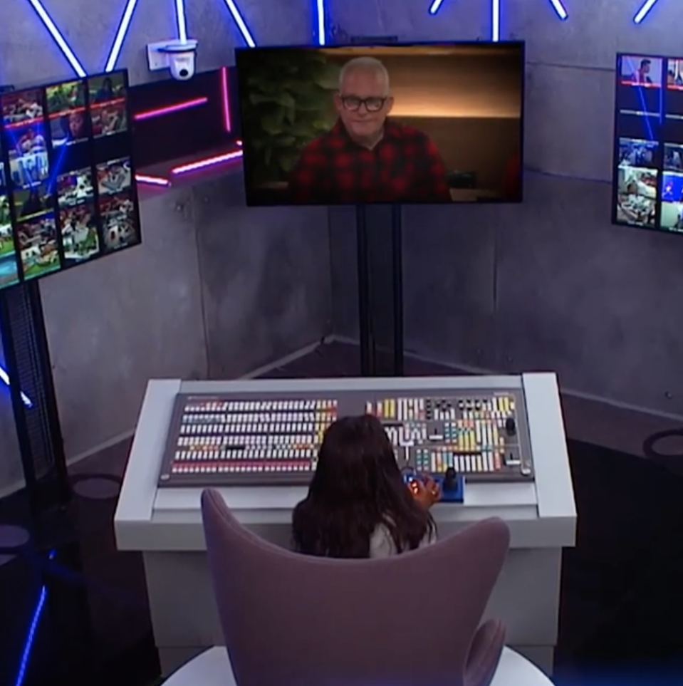 Angela seated at a control panel in front of various TV screens in Big Brother's bunker