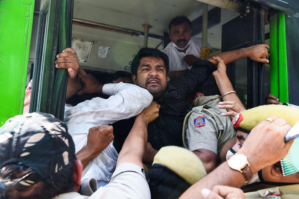 Police push Congress Party activists into a bus after detaining them during an anti-government demonstration to protest against the recent passing of new farm bills in parliament in New Delhi on September 28, 2020. (Photo by Sajjad HUSSAIN / AFP) (Photo by SAJJAD HUSSAIN/AFP via Getty Images)