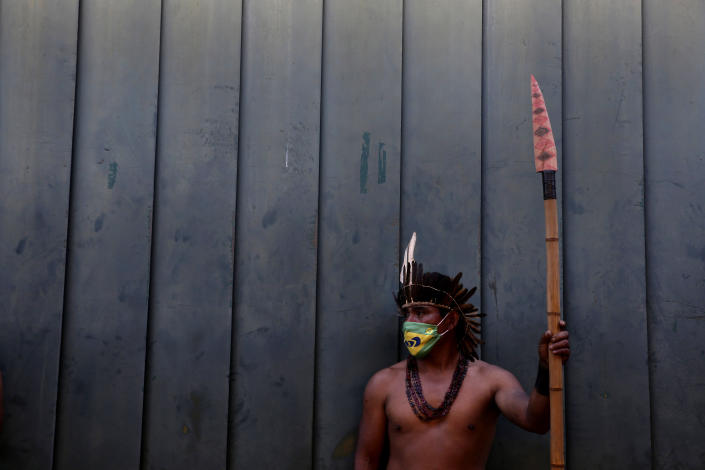 An Indigenous man wearing a protective face mask amid the COVID-19 pandemic takes part in a protest against Brazilian President Jair Bolsonaro's proposals to allow mining on Indigenous lands, at the main entrance to the Chamber of Deputies in Brasilia, Brazil, Wednesday, June 9, 2021. (AP Photo/Eraldo Peres)