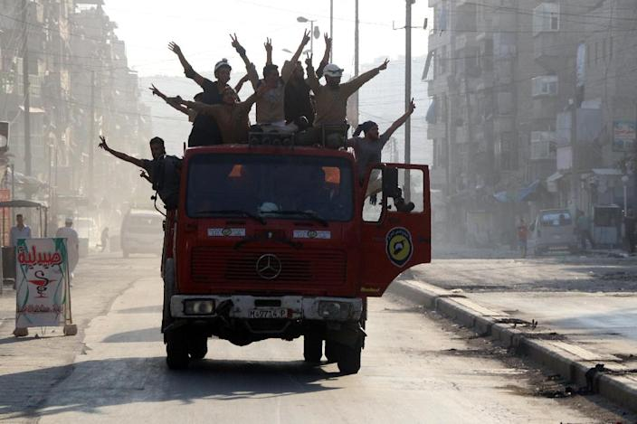 Syrian civil defence volunteers, known as the White Helmets, celebrate in a street in the northern city of Aleppo on August 6, 2016 (AFP Photo/Thaer Mohammed)