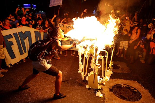 A girl spits fire on a bus turnstile set on a street in protest against the increase on bus fares in Rio de Janeiro, Brazil, Monday, Feb. 10, 2014. Anti-government protests erupted across Brazil last June, hitting their peak as 1 million Brazilians took to streets on a single night, calling for better schools and health care and questioning the billions spent to host this year's World Cup and the 2016 Olympics. The protests have since diminished in size, but remain violent. (AP Photo/Leo Correa)