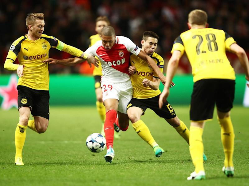 Mbappe tries to make his way through a group of Dortmund players (Getty)