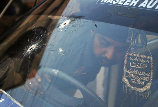 A Pakistani police officer examines a bullet-riddled police vehicle following an attack by gunmen in Karachi on Thursday. A suicide bomber targeted a police official in Pakistan's financial capital , killing at least three people and wounding 13 others, police said