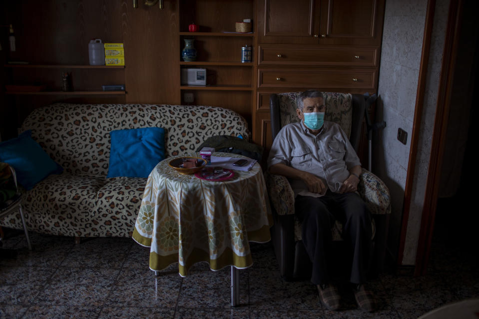 Vicente Lopez, 65, sits at his house waiting to be examined by a doctor during a home care visit in Barcelona, Spain, March 31, 2020. Lopez is under quarantine, because his partner tested positive for COVID-19 and is in the hospital. Lopez relies on a neighbor to deliver groceries and basic supplies. (AP Photo/Emilio Morenatti)