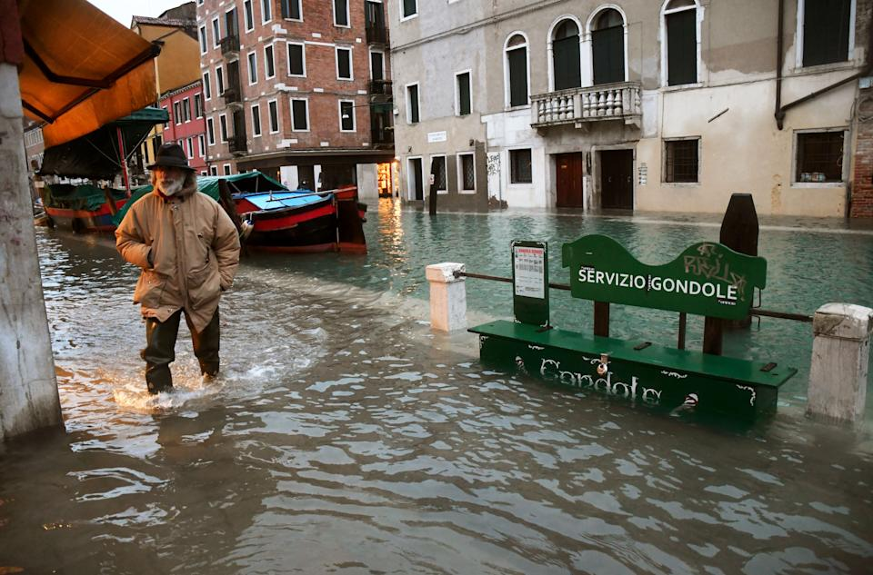 "A man walks across a flooded canal on December 8, 2020 in Venice following a high tide ""Alta Acqua"" event following heavy rains and strong winds, and the mobile gates of the MOSE Experimental Electromechanical Module that protects the city of Venice from floods, were not lifted (Photo by ANDREA PATTARO / AFP) (Photo by ANDREA PATTARO/AFP via Getty Images)"