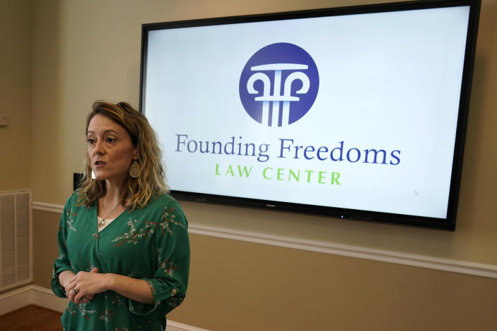 Hanover County resident Sarah Via gestures during a news conference at The Family foundation offices in Richmond, Va., Tuesday, March 30, 2021. Via commented on the filing of a lawsuit challenging the state Department of Education's newly issued guidelines on the treatment of transgender students. (AP Photo/Steve Helber)