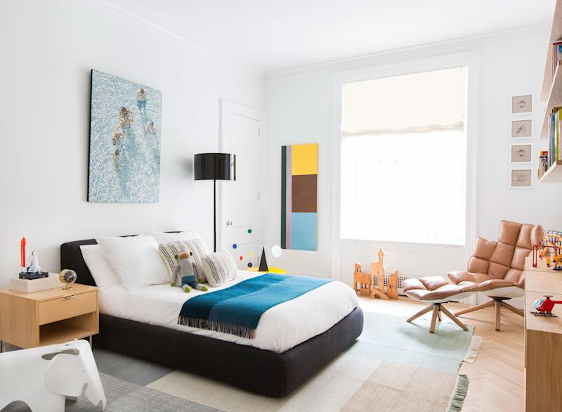 """In this bedroom, designed for a young boy, a charcoal-hued storage bed from Design Within Reach was paired with a tan leather armchair and footrest by Patricia Urquiola for B&B Italia. """"This bed is very useful; you can flip it open and put away toys in there,"""" says Grehl. """"You never have enough storage in Manhattan, even in a 5,000-square-foot apartment."""" The Pointillist painting behind the bed is by William Betts, and the geometric one next to the window is by Albert Stadler."""