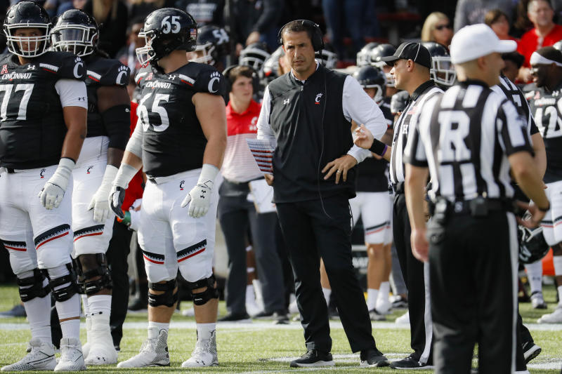 Cincinnati head coach Luke Fickell, center, speaks to a referee during the first half of an NCAA college football game against Tulsa, Saturday, Oct. 19, 2019, in Cincinnati. (AP Photo/John Minchillo)