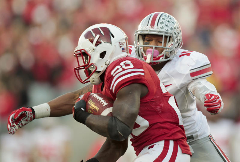 Ohio State's Ryan Shazier (10) wraps up Wisconsin running back Montee Ball during the first half of an NCAA college football game Saturday, Nov. 17, 2012, in Madison, Wis. (AP Photo/Andy Manis)