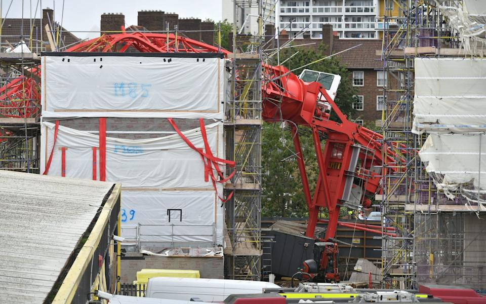 The crane lying on top of the block of flats under construction - Dominic Lipinski/PA