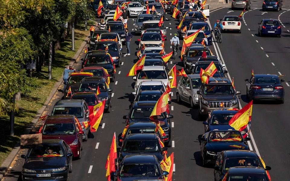 Demonstrators in Madrid protest against the national Government, which declared a state of emergency in the capital to restrict mobility - Getty