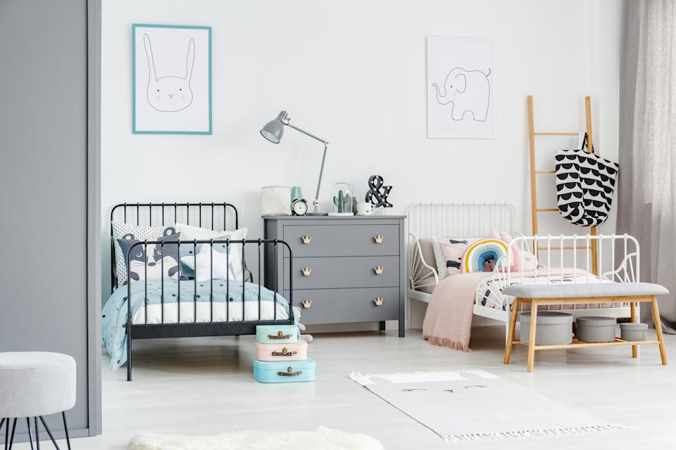 White bed for a girl and black one for a boy in a siblings  bedroom interior with posters of a rabbit and an elephant on a white wall. Simple scandi design. Real photo