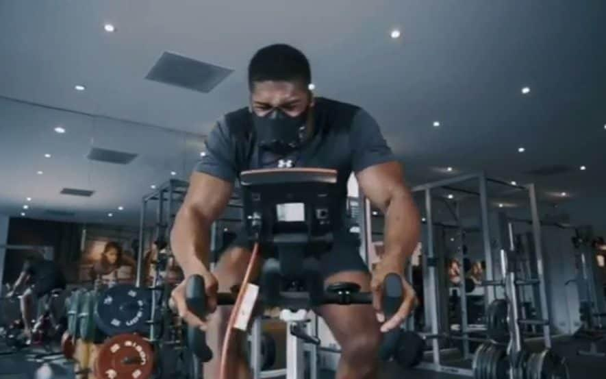 Joshua gives it some large on the exercise bike in the gym, in a video posted to his Instagram with him wearing an altitude mask - Credit: @anthony_joshua/Instagram