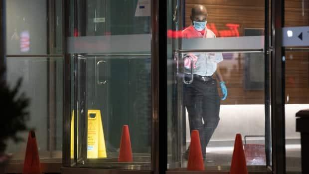 A worker cleans the door handle of a downtown office building. Current wage subsidy programs don't meet the needs of workers who do not have employer-sponsored benefits and who cannot afford to miss work due to mild symptoms if they will lose income, Dr. Anne Huang writes. (Andrew Lee/CBC - image credit)