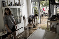 Homeowners push mud and water out of their house after flooding in Angleur, Province of Liege, Belgium, Friday July 16, 2021. Severe flooding in Germany and Belgium has turned streams and streets into raging torrents that have swept away cars and caused houses to collapse. (AP Photo/Valentin Bianchi)