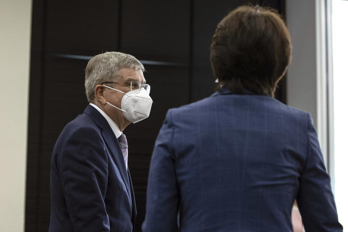 IOC President Thomas Bach, left, is greeted by Tokyo 2020 President Seiko Hashimoto, right, during their meeting at the Tokyo 2020 Headquarters Tuesday, July 13, 2021 in Tokyo, Japan. Bach has appeared in public for the first time since arriving in Tokyo with the pandemic-postponed Olympics opening in just 10 days.(Takashi Aoyama/Pool Photo via AP)