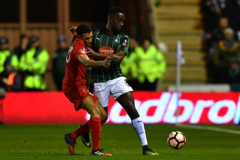 Plymouth Argyle striker Jordan Slew is tackled by Trent Alexander-Arnold in an FA cup match in 2017 - Plymouth have raised the money to commemorate Jack Leslie, a black player from the 1920s