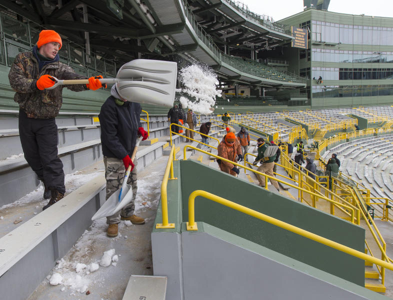 Workers clear ice and snow from the seats at Lambeau Field on Friday, Jan. 3, 2014, in Green Bay, Wis. in preparation for Sunday's NFL football wild-card playoff game between the Green Bay Packers and San Francisco 49ers.(AP Photo/Mike Roemer)