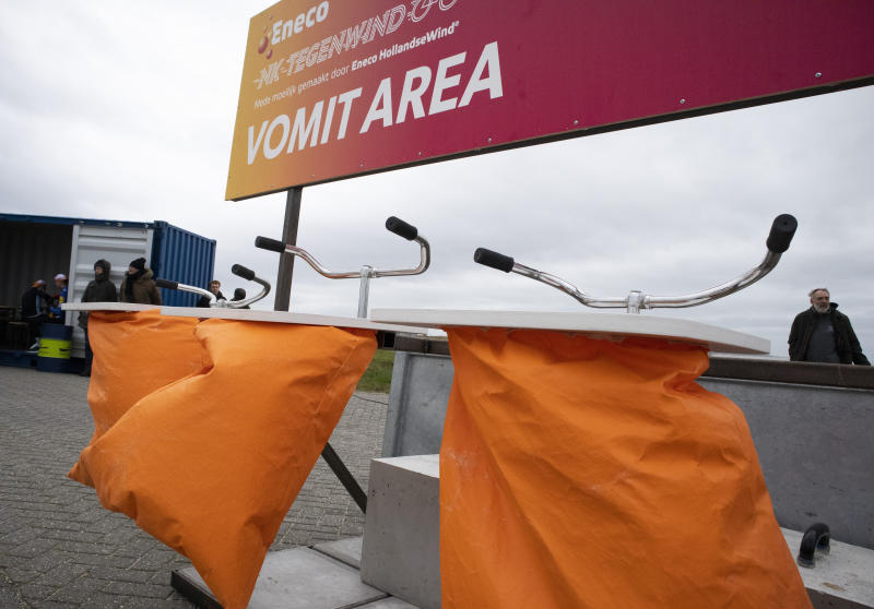 Bicycle handle bars serves as support over a bucket at the vomit area on the finish line of the Dutch Headwind Cycling Championships on the storm barrier Oosterscheldekering near Neeltje Jans, south-western Netherlands, Sunday, Feb. 9, 2020. (AP Photo/Peter Dejong)