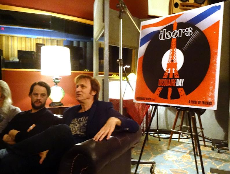 Michael Kurtz (R), co-founder of Record Store Day, and Lee Foster (L), manager of Electric Lady Studios, sit next to a poster advertising a special release by The Doors during a news conference on March 8, 2016 (AFP Photo/Shaun TANDON)