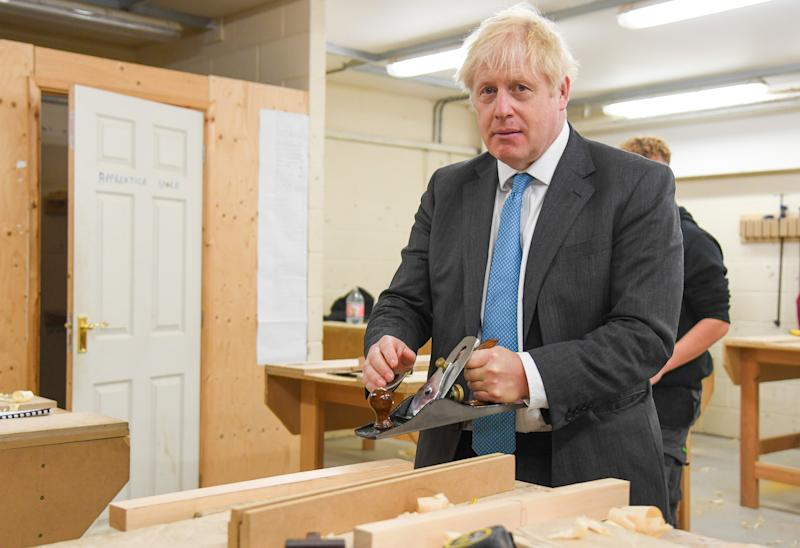"""Britain's Prime Minister Boris Johnson uses a plane as he talks with carpentry students in a wood working class aduring his visit to Exeter College in Exeter, southwest England on September 29, 2020. - British Prime Minister Boris Johnson revealed Tuesday he was obese when he contracted the novel coronavirus COVID-19 earlier this year, but after losing weight said he now felt much better. """"I am fitter than I was before, it may irritate you to know,"""" he said, when asked by a reporter about his health following a speech on education. (Photo by Finnbarr Webster / POOL / AFP) (Photo by FINNBARR WEBSTER/POOL/AFP via Getty Images)"""