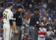 Umpire Lazaro Diaz (63) removes the glove of Milwaukee Brewers pitcher Jake Cousins (54) during the seventh inning of a baseball game against the St. Louis Cardinals, Thursday, Sept. 23, 2021, in Milwaukee. (AP Photo/Jeffrey Phelps)