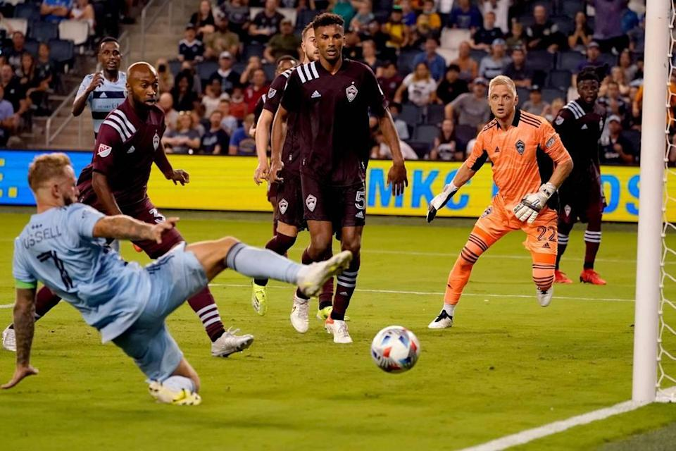 Sporting Kansas City forward Johnny Russell (left) takes a shot that was blocked by Colorado Rapids defender Auston Trusty during the second half of an MLS soccer match Saturday, Aug. 28, 2021, at Children's Mercy Park in Kansas City, Kan.