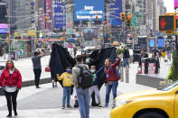 Visitors to New York's Time Square pose for a photo with a street performer working for tips dressed as Batman, Tuesday, April 27, 2021. In recent weeks, tourism indicators for New York City like hotel occupancy and museum attendance that had fallen off a pandemic cliff have ticked up slightly. It's a welcome sight for a city where the industry has been decimated by the impact of the coronavirus. (AP Photo/Mary Altaffer)