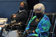 Virginia State Sen. Maime Locke, D-Hampton, left, listens along with Sen. Louise Lucas, D-Portsmouth, right, during debate on a bill calling for the removal of the statue of former Senator Harry F. Byrd Sr. from Capitol Square during the Senate session at the Science Museum of Virginia in Richmond, Va., Tuesday, Feb. 23, 2021. The Senate passed the measure. (AP Photo/Steve Helber)