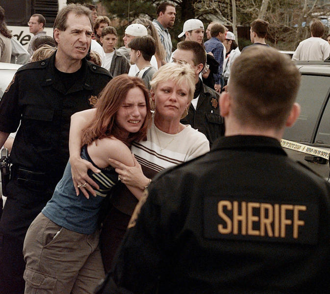 FILE - In this April, 20, 1999, file photo, a woman embraces her daughter after they were reunited following a shooting at Columbine High School in Littleton, Colo. The shooting shocked the country as it played out on TV news shows from coast to coast. Images from the scene showed terrified students fleeing the school, SWAT officers waiting to enter and an injured boy trying to escape through a window. (AP Photo/Ed Andrieski, File)