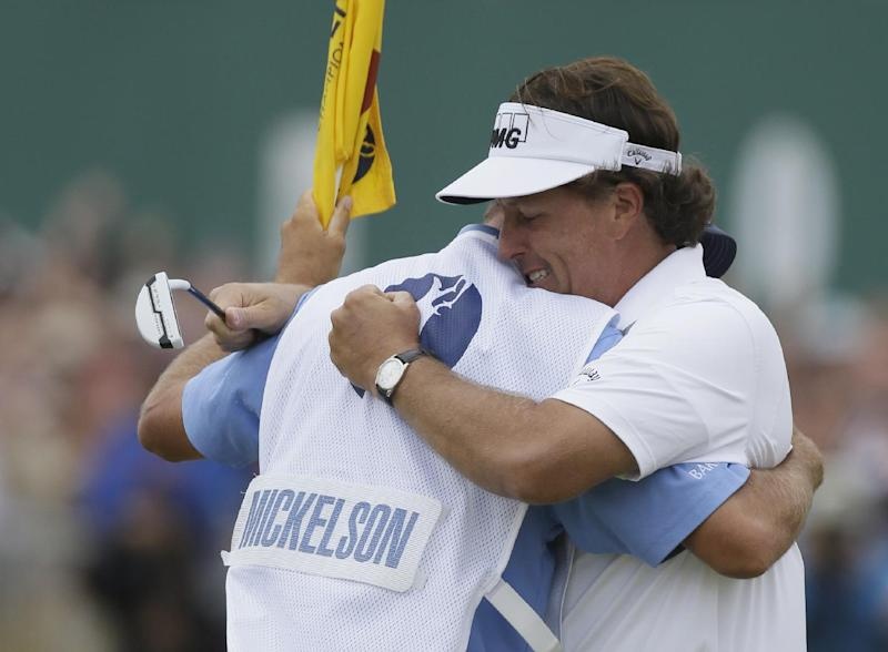 Phil Mickelson of the United States celebrates after his final putt on the 18th green with his caddie Jim Mackay during the final round of the British Open Golf Championship at Muirfield, Scotland, Sunday July 21, 2013. (AP Photo/Jon Super)