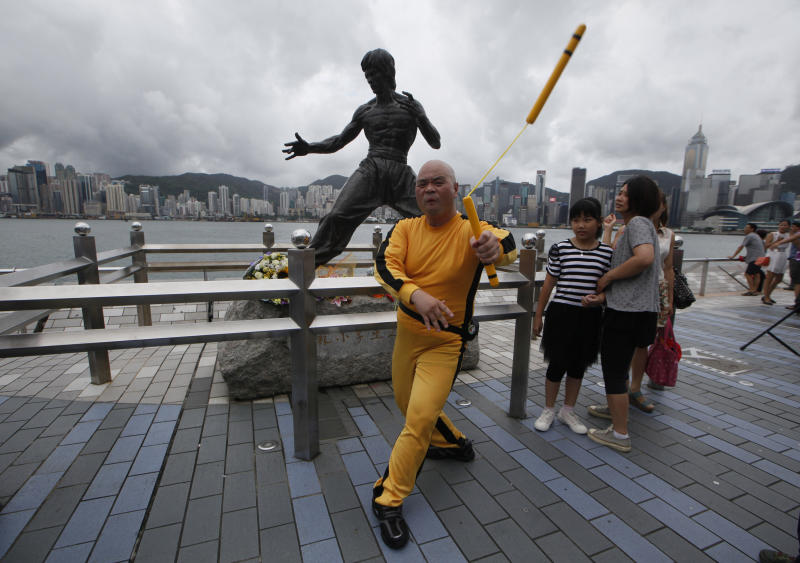 "A Japanese fan Kazuo Abe dressing as the late Hong Kong Kung Fu star Bruce Lee shows his skill of Nunchaku in front of the Lee's bronze statue in Hong Kong Saturday July 20, 2013 to commemorate the 40th anniversary of his death. The late superstar Bruce Lee is best-known for the kung fu skills he displayed in his movies, but his daughter hopes that more people take the effort to understand his teachings and life philosophy. Marking his death 40 years ago on July 20, the Hong Kong government has teamed up with the Bruce Lee Foundation to put together an exhibition to showcase the late star's life, from his famous yellow tracksuit he wore in the movie ""Game of Death,"" to his writings and drawings. (AP Photo/Kin Cheung)"