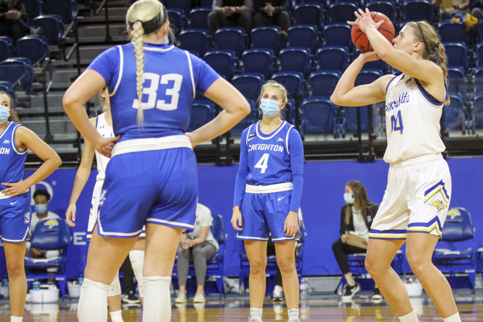 This photo provided by South Dakota State Athletics shows Creighton women's college basketball player Temi Carda (4), second from right, wearing a mask while an unidentified South Dakota State player shoots a free throw during an NCAA college basketball game in Brookings, South Dakota, Monday, Nov. 30, 3030. It's a common sight to see players and coaches wear masks on the sideline so far this season during college basketball games to help prevent the spread of the coronavirus. The DePaul and Creighton women's basketball teams are among a few squads that have taken it a step further with their players wearing the masks while they are on the court playing.(Christian Gravius/South Dakota State Athletics via AP)