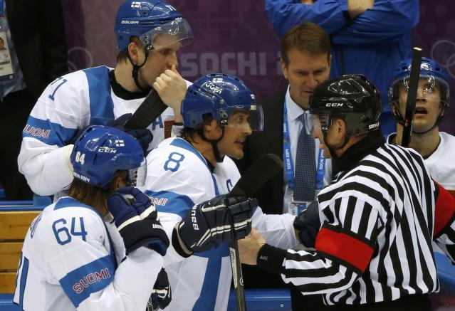 Finland's Teemu Selanne (8) talks to the referee as teammates Mikael Granlund (64) and Leo Komarov listen in during the first period of their men's ice hockey bronze medal game against Team USA at the Sochi 2014 Winter Olympic Games February 22, 2014. REUTERS/Grigory Dukor (RUSSIA - Tags: SPORT ICE HOCKEY OLYMPICS)
