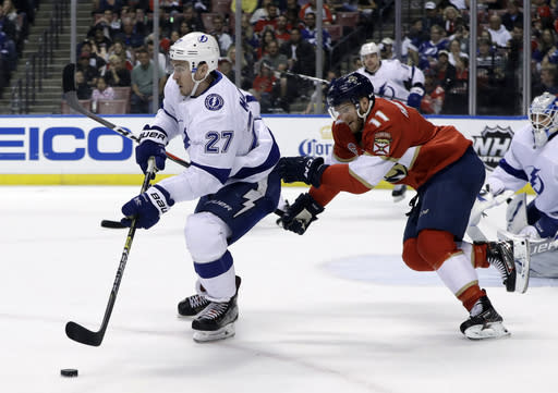 Tampa Bay Lightning defenseman Ryan McDonagh (27) skates with the puck as Florida Panthers left wing Jonathan Huberdeau (11) pursues during the second period of an NHL hockey game, Sunday, Feb. 10, 2019, in Sunrise, Fla. (AP Photo/Lynne Sladky)