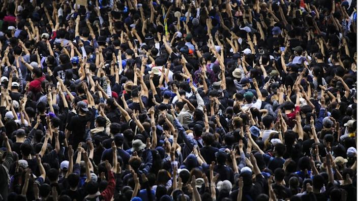Pro-democracy protesters flash three-finger salute during an anti-government protest in Bangkok, Thailand, 17 October 2020