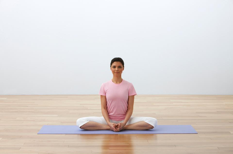 """This pose helps to open the hips and ease sciatica discomfort that can be made worse by sitting for long periods.  Sit up tall with the soles of the feet touching and knees spreading open, bringing the feet in toward the pelvis and clasping your hands around your feet. Flap the knees up and down several times like butterfly wings, then sit still and focus the weight of the hips and thighs into the floor, easing pain in the sciatic nerve.  """"The sciatic nerve starts in the lower back and runs down both leg, and sciatic nerve pain can occur when the nerve is somehow compressed,"""" Bielkus says. """"Long commutes and sitting for long periods of time exacerbates it."""""""