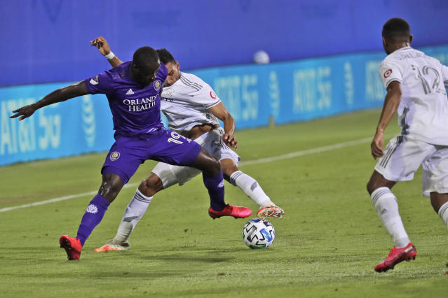 Orlando City forward Benji Michel (19) battles for the ball with Los Angeles FC defender Eddie Segura, left, as Los Angeles FC defender Diego Palacios (12) closes in during the second half of an MLS soccer match Friday, July 31, 2020, in Orlando, Fla. (AP Photo/John Raoux)