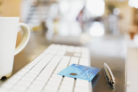 A blue bank card on top of a computer keyboard
