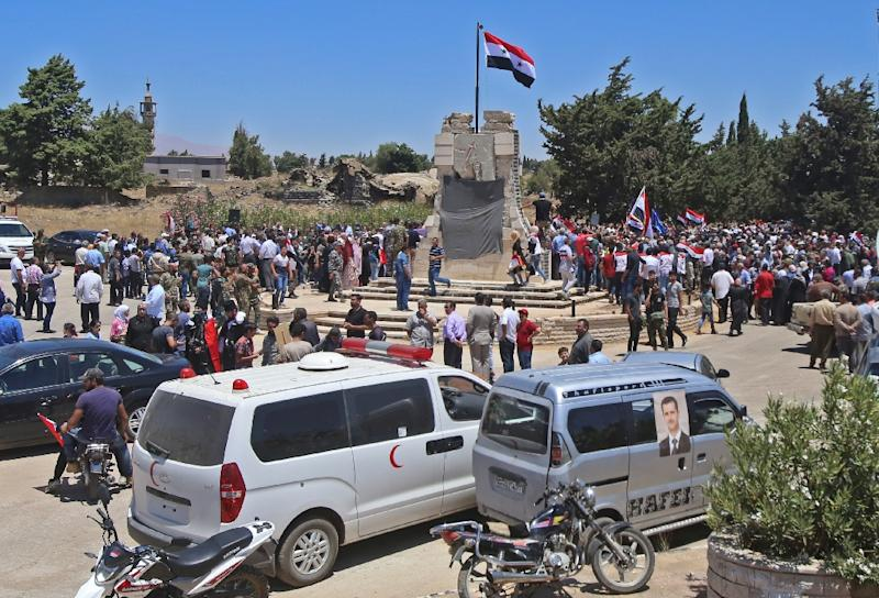 Syrian soldiers raise the national flag in the town of Quneitra in the Syrian Golan Heights