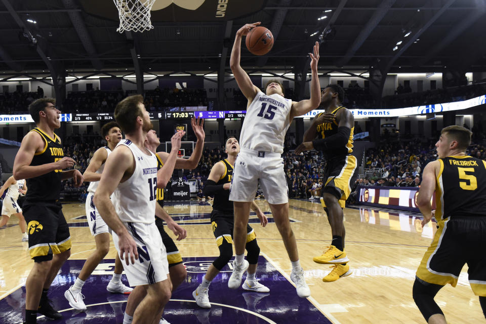 Northwestern center Ryan Young (15) grabs a rebound during the first half of the team's NCAA college basketball game against Iowa on Tuesday, Jan. 14, 2020, in Evanston, Ill. (AP Photo/David Banks)