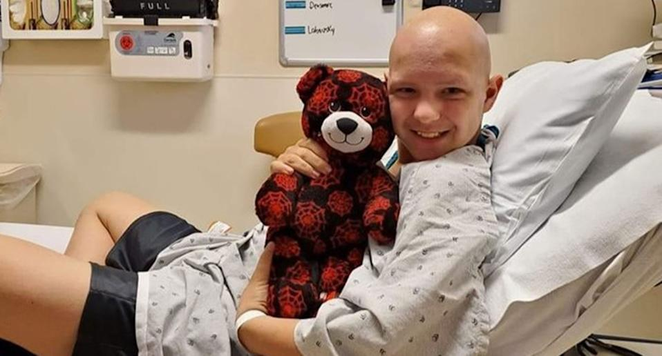 Michael Choroszy, 11, is pictured holding a teddy bear in a hospital bed.