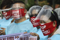 Protesters wear face masks with slogans before marching towards the House of Representative where Philippine President Rodrigo Duterte is set to deliver his final State of the Nation Address in Quezon city, Philippines on Monday, July 26, 2021. Duterte is winding down his six-year term amid a raging pandemic and a battered economy. (AP Photo/Gerard Carreon)