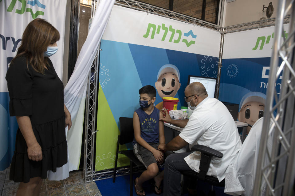 FILE - In this Aug. 15, 2021, file, photo, a 12-year-old boy braces himself as a medical professional prepares to administer the coronavirus vaccine at Clalit Health Services, one of Israel's health maintenance organizations, in Jerusalem. Israel is pressing ahead with its aggressive campaign of offering coronavirus boosters to almost anyone over 12 and says its approach was further vindicated by a U.S. decision to give the shots to older patients or those at higher risk. (AP Photo/Maya Alleruzzo, File)