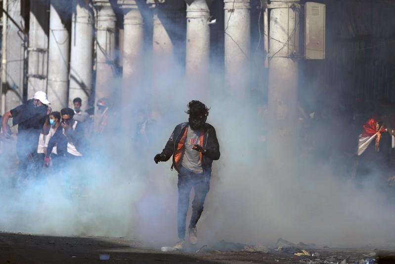 An Iraqi demonstrator runs from tear gas during the ongoing anti-government protests in Baghdad