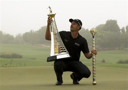 Stenson of Sweden poses with his trophies after winning the DP World Tour Championship in Dubai