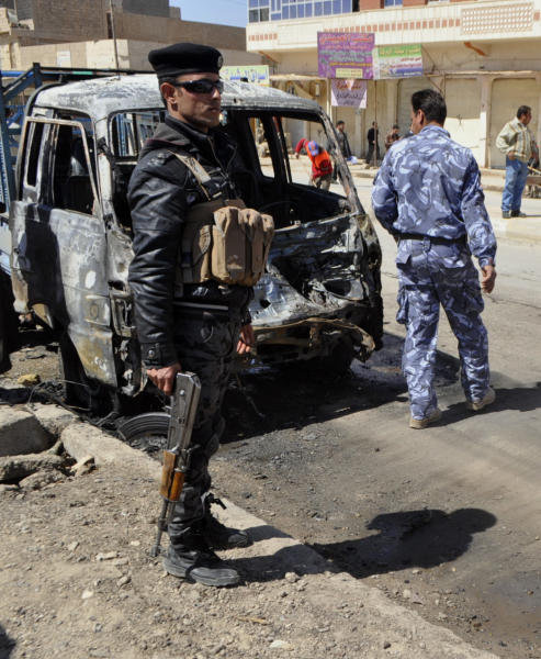 Security forces inspect the scene of a car bomb attack in Ramadi, 70 miles (115 kilometers) west of Baghdad, Iraq, Tuesday, March 20, 2012. Officials say attacks across Iraq have killed and wounded scores of people in a spate of violence that was dreaded in the days before Baghdad hosts the Arab world's top leaders. (AP Photo)