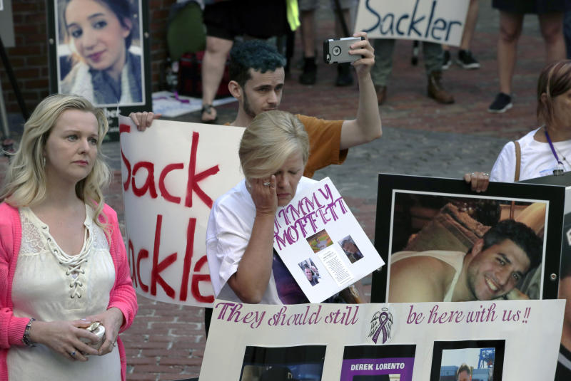 Protesters, including Carol Lorento, center, gather outside a courthouse on Friday, Aug. 2, 2019, in Boston, where a judge was to hear arguments in Massachusetts' lawsuit against Purdue Pharma over its role in the national drug epidemic. Organizers said they wanted to continue to put pressure on the Connecticut pharmaceutical company and the Sackler family that owns it.  (AP Photo/Charles Krupa)